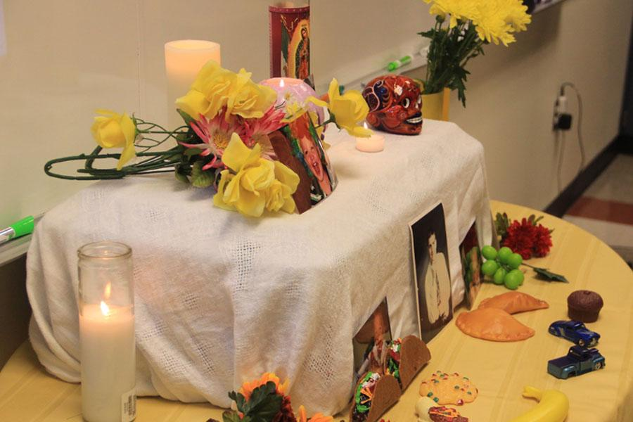 Students pretend to set up decorations on the altar for honoring the dead.  The altar included food, candles, pictures, and other knickknacks.
