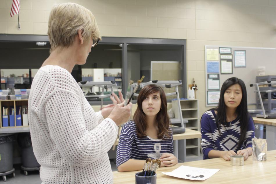 Mrs. Maureen Yaeger, Art,  tells Anna Hallowell (10) and Jessica Rogers (10) what the project of the month will be and how to finish. Mrs. Yaeger helped the girls when they had a question.