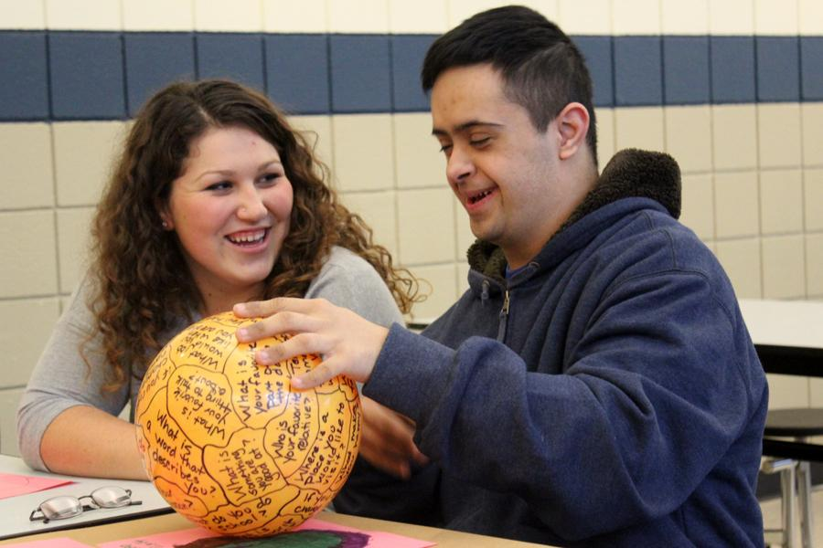 "Kiera Schultz (12) and Ehsan Raja (11) laugh together while getting to know each other.  The beach ball had questions written on it such as ""What is your favorite movie?"""