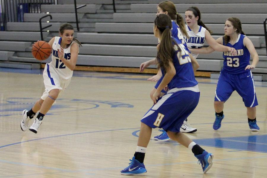 Kylie Exton (10) dribbles the ball across the court to her team's side. Her team won the game against Highland 58-21.