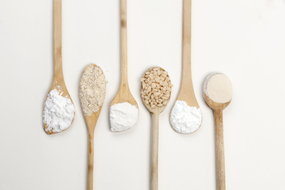 Six spoons hold ingredients used in gluten-free cooking. Gluten-free ingredients include starches, flours and rice cereal.