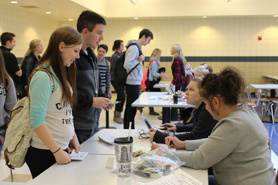 Tara DeGrauwe (11) and Spencer Wise (11) purchase their tickets in the cafeteria.  They were finally able to do this after waiting in the long line after school on Wednesday.