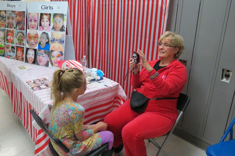 Ms. Donna Davis, worker at Face Painting, takes a picture of the face painting she gave to a child at the craft show. The face painting stand was set up in the morning of Nov. 21.