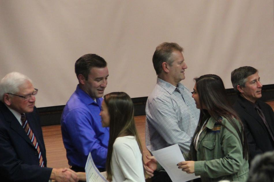 Jennifer Chavarria (10) shakes hands with the school board members in congratulations for the awards.