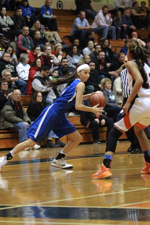 Victoria Gard (11) dribbles hard around a West Side defender.  The Indians beat the Cougars 75-65.