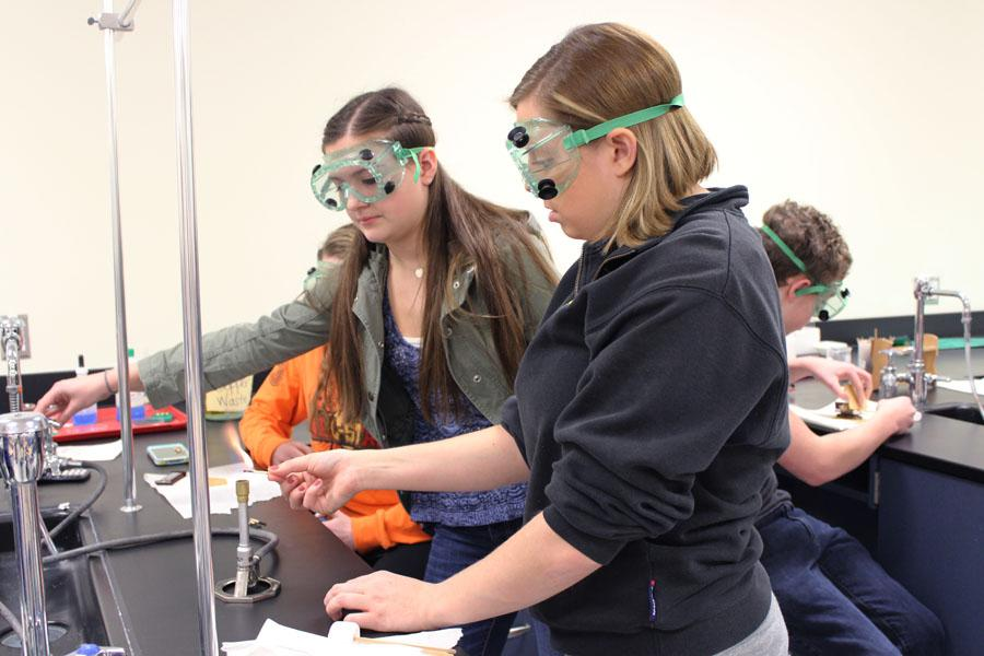 Ms. Lauryn Beneturski, Science, helps Alexandra Idalski (10) light her Bunsen Burner.  Both Ms. Beneturski and Idalski had to wear protective goggles so they would not accidentally damage their eyes from the flame.