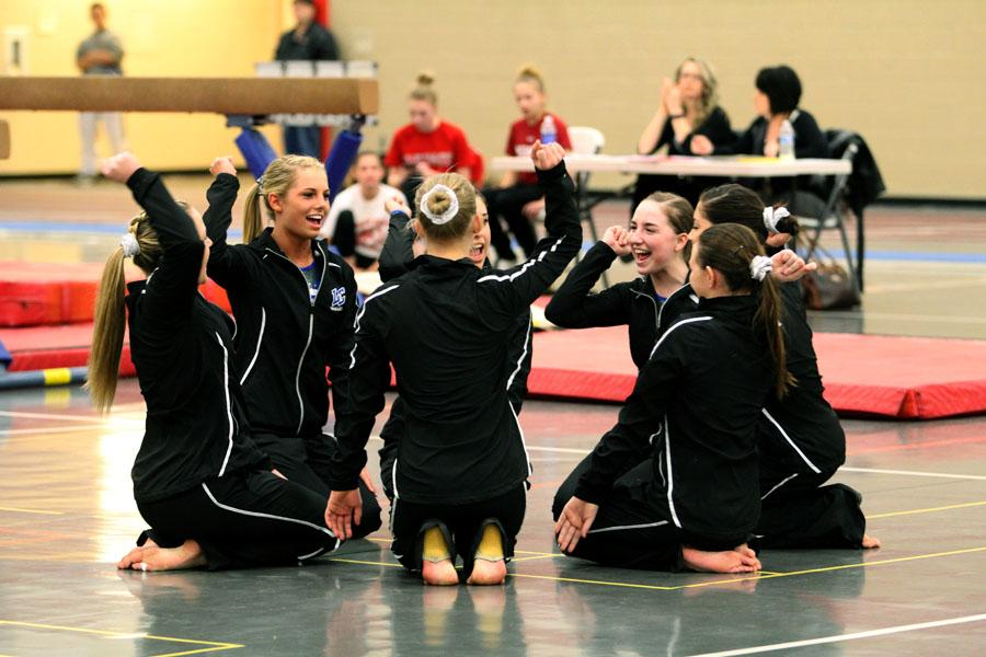 The gymnastic team performs their routine cheer before the competition started.  The cheer was meant to start off the meet and keep the girls spirits up.