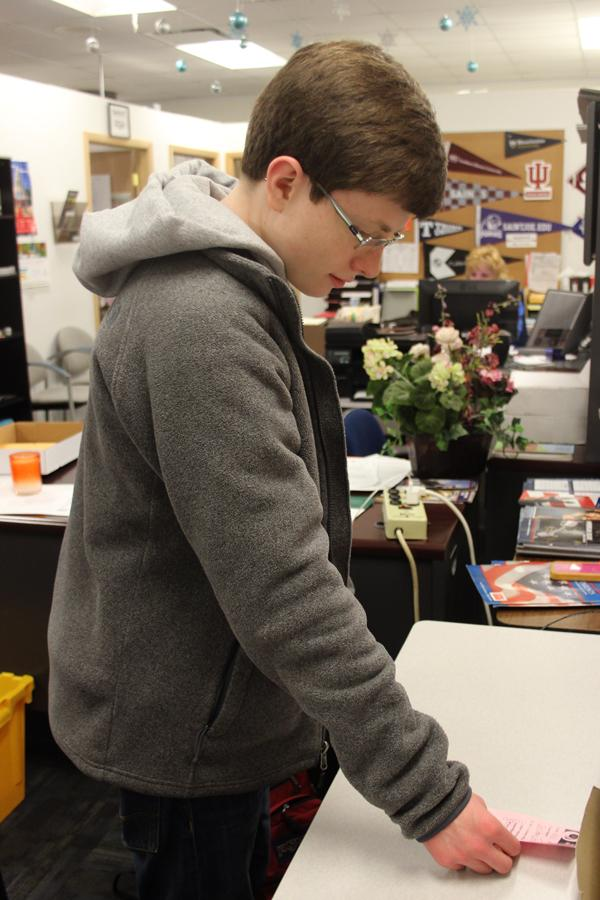 Sean Meyer (11) picks up a guidance pass to deliver to a student. Meyer has been aiding since the beginning of his sophomore year, and plans to continue next year.