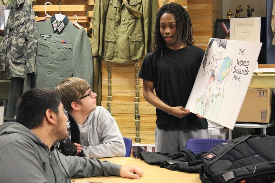Gabriel Henderson (11) shows his friends the World War II propaganda poster he made for his U.S. History class. Several members of the History Club were amazed by the detail and historical accuracy that was encompassed in the piece.