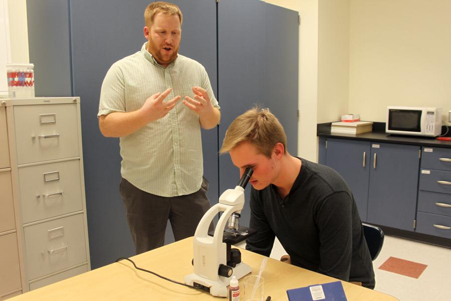 Dr.+Dustin+Verpooten%2C+Science%2C+helps+Marc+Mertsching+%2812%29+look+through+a+microscope.+Mertsching+was+using+the+microscope+in+Dr.+Verpooten%E2%80%99s+AP+biology+class.