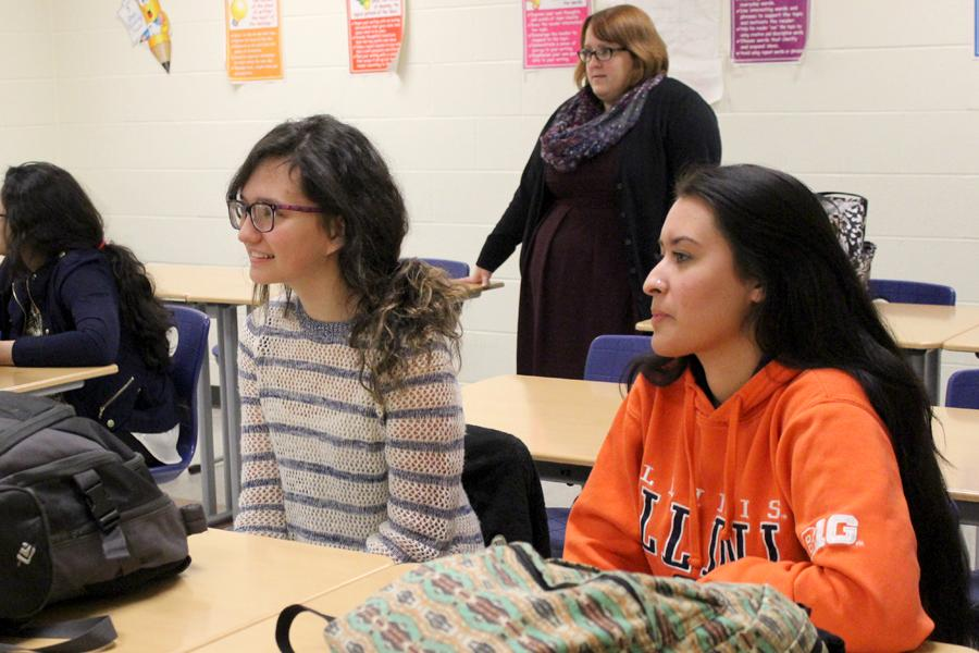 Maria Moricz (11) and Emily Segovia (11) listen to their club sponsors as the meeting starts. During the meeting, the club decided on a final color scheme and Prom favors.