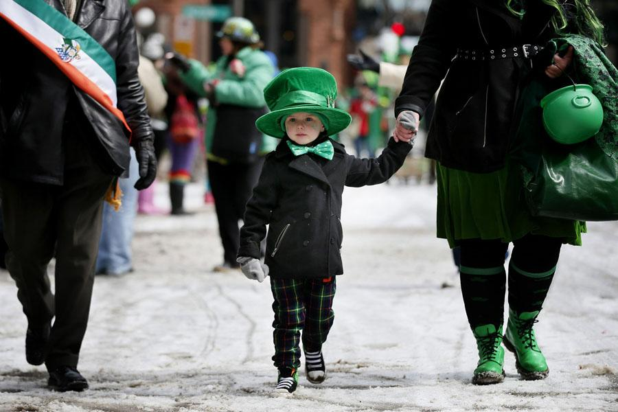 A young boy holds onto his mother's hand during a St. Patrick's Day parade.  This year, the holiday falls on a Tuesday on March 17.