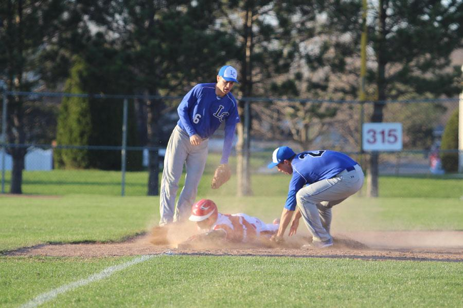 Alexander Nisle (12) tags the opponent at third base causing an out. The win put the boys tied for first along with Crown Point in the DAC conference.