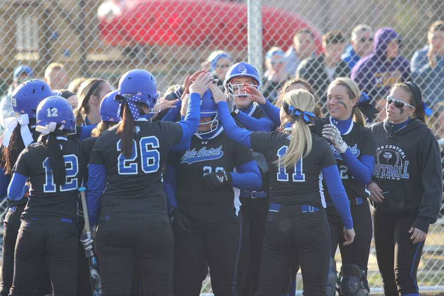 The varsity softball team celebrates a home run from Julia Schassburger (11). Schassburger, the starting pitcher, helped her team by scoring three runs in a single at bat.