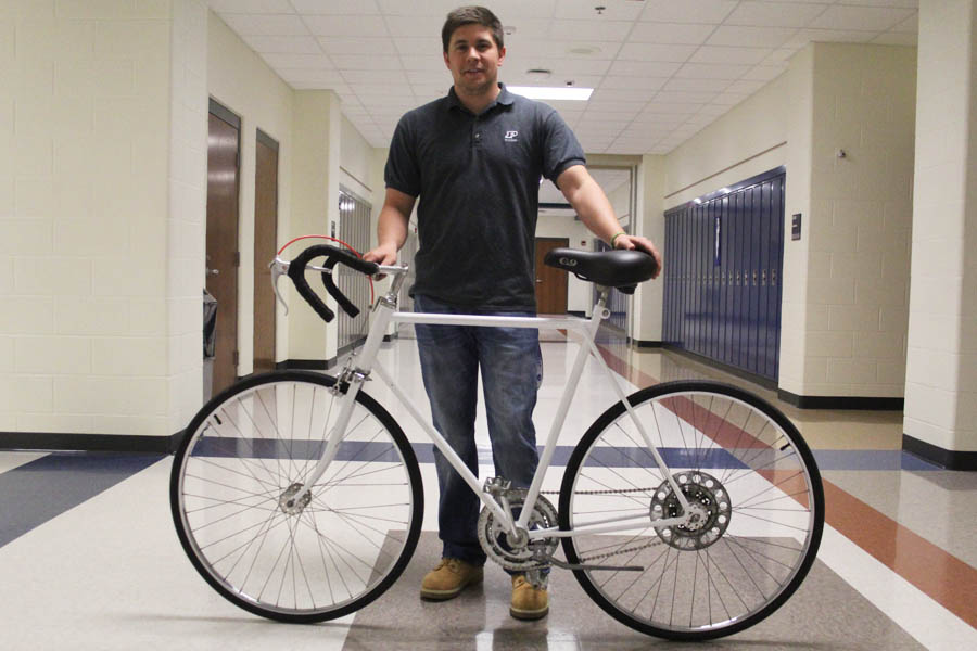 Mr.+Eric+Graves%2C+Math%2C+poses+in+the+hallway+with+his+bike+that+he+rides+to+and+from+school.+The+bike%2C+which+was+in+poor+condition+when+Graves+originally+discovered+it%2C+has+been+restored+by+him+and+is+now+used+as+a+means+of+transportation%2C+exercise+and+a+way+to+save+money.