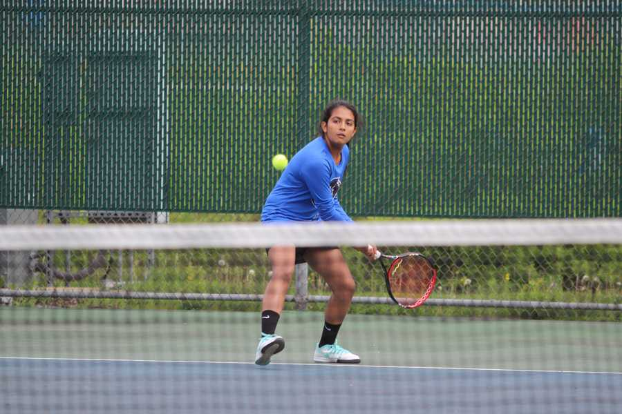 Navneet Kaur (12) swings to hit the ball as it approaches her side of the court. Kaur maintained focus as she watched the ball.