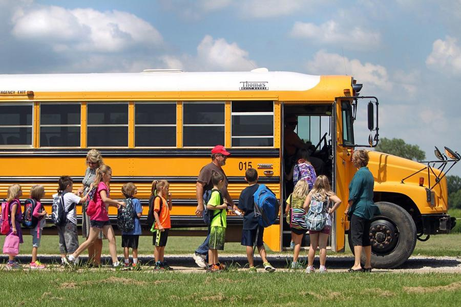 Students+board+a+bus+on+the+first+day+of+school+in+Bates+County%2C+Missouri%2C+on+August+14%2C+2013.+Miami+R-1+Elementary+School+has+started+a+four-day+school+week+adding+about+half+an+hour+to+the+other+days+and+is+embracing+technology+such+as+iPads+in+the+classroom.+%28Tammy+Ljungblad%2FKasas+City+Star%2FMCT%29