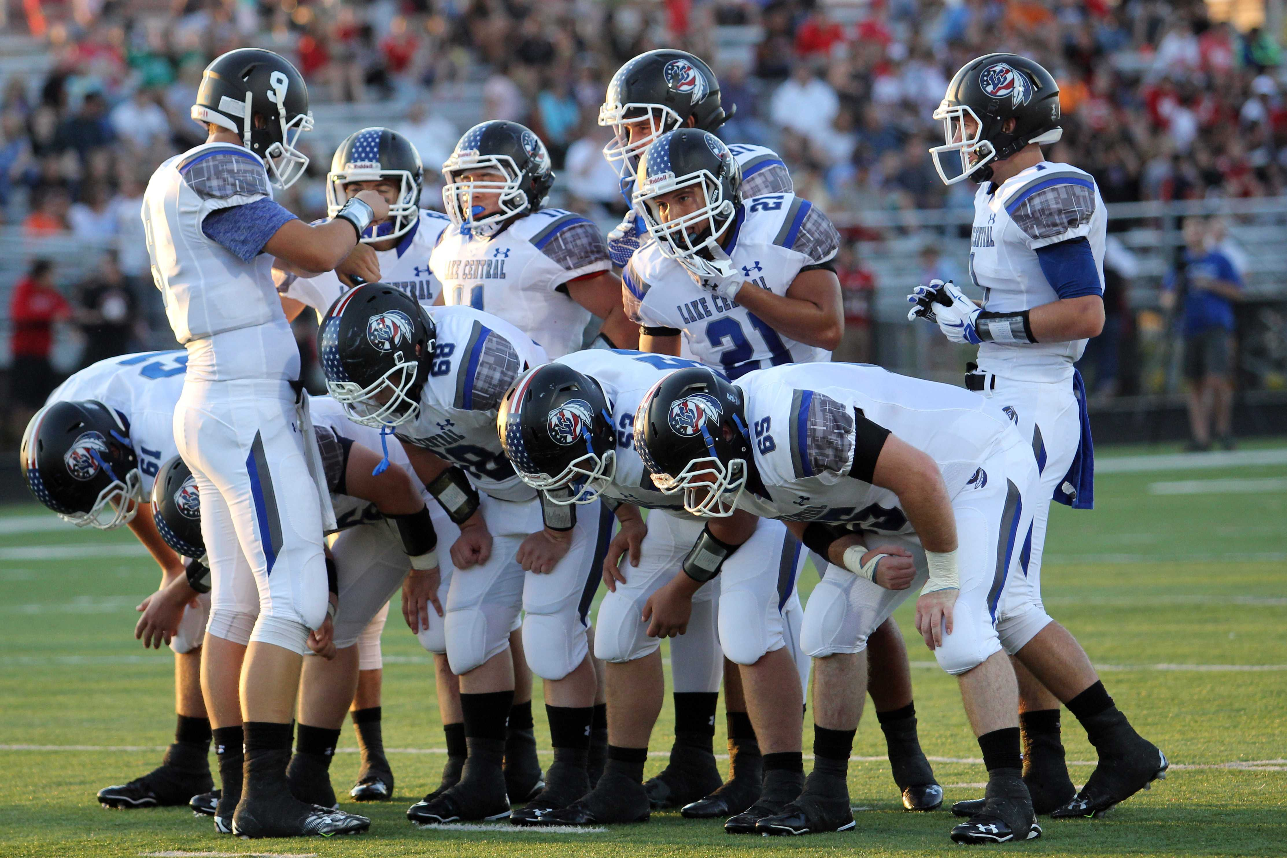 Ethan Darter (12) gives the play in the huddle. Darter ended the game with 19 of 25 for 206 yards.