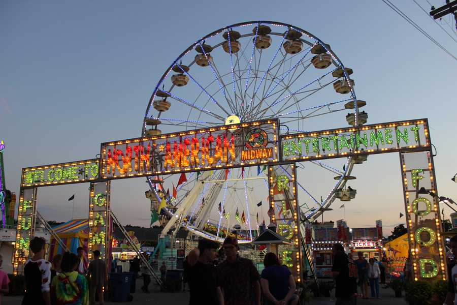 The Lake County Fair's Ferris wheel spins attendees around behind an entrance to the carnival area.  The lights from the wheel and other fair rides lit up the evening sky.
