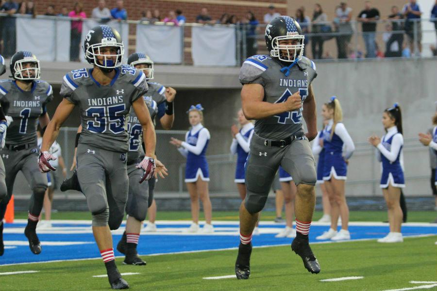 Nicholas Lucas (11) and Daniel Heinrikson (12) lead the team onto the field at the start of the game. This was the first game home game of the season.