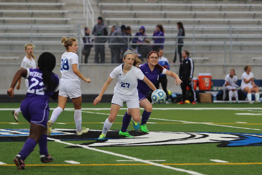 Jenna Galvan (9) gets ready to kick the incoming soccer ball. Galvan played defense during the game.