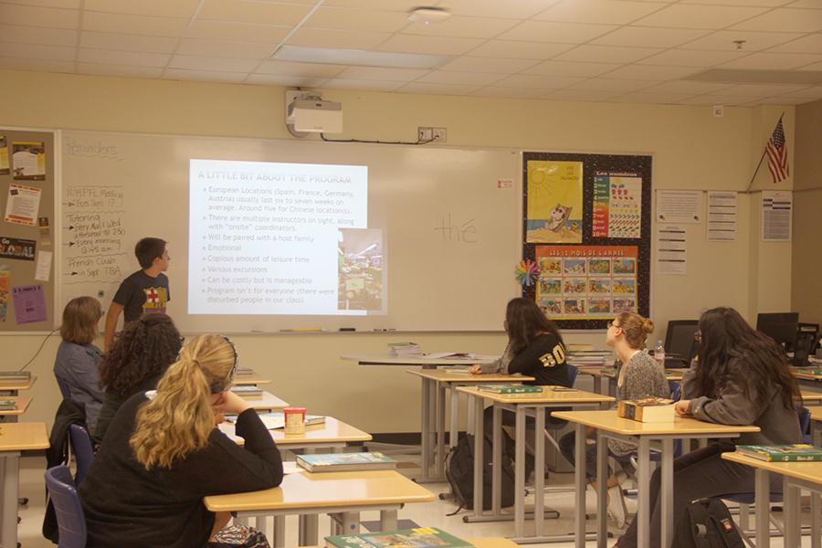 Joshua Sterne (12) presents his trip from this past summer. Attendees to the meeting were Mrs. Nancy Tilka, World Language, Nyia Guy (11), Emma DeGroot (11), Leslie Lopez (12), Emily Hansen (12), and Elise Classen (12).