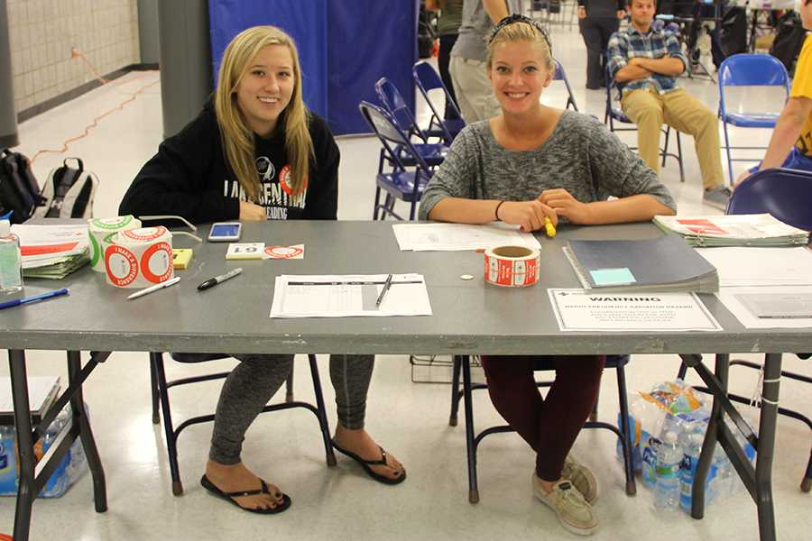 Kennedy Moore (12) and Abigail Keith (12) sit at the front table at the Blood Drive to check students in before they donate. Both girls are volunteers from the National Honor Society.