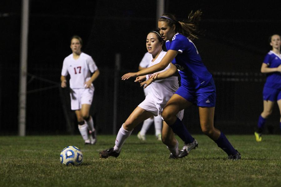 Sydney Dragos (10) fights to get past the Munster player to reach the ball. The Indians fought for a chance to score in the second half, chasing Munster's lead of 2-1.