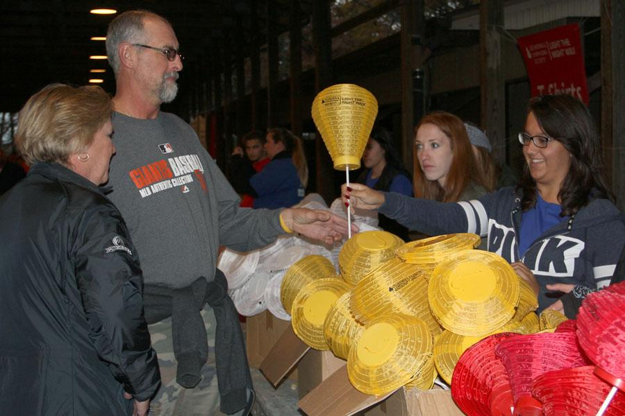 Breanna Dobos (12) hands a walker a gold lantern in remembrance of someone who did not survive blood cancer. She volunteered at the walk as a representative of NHS.