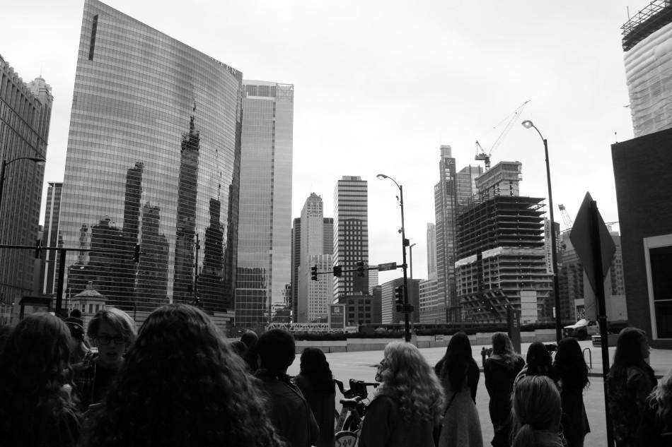 The buildings reflect off of the skyscraper on the overcast day. The students finished shopping and waited for their bus to arrive.