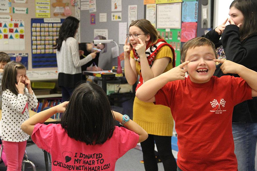 """One of the elementary students goofs off while learning """"Head, Shoulders, Knees and Toes."""" The students had a lot of fun during the visit from the German IV students."""