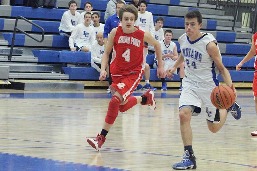 Zachary+Dobos+%289%29+dribbles+the+ball.+Dobos+was+heading+toward+to+basket+to+score.+