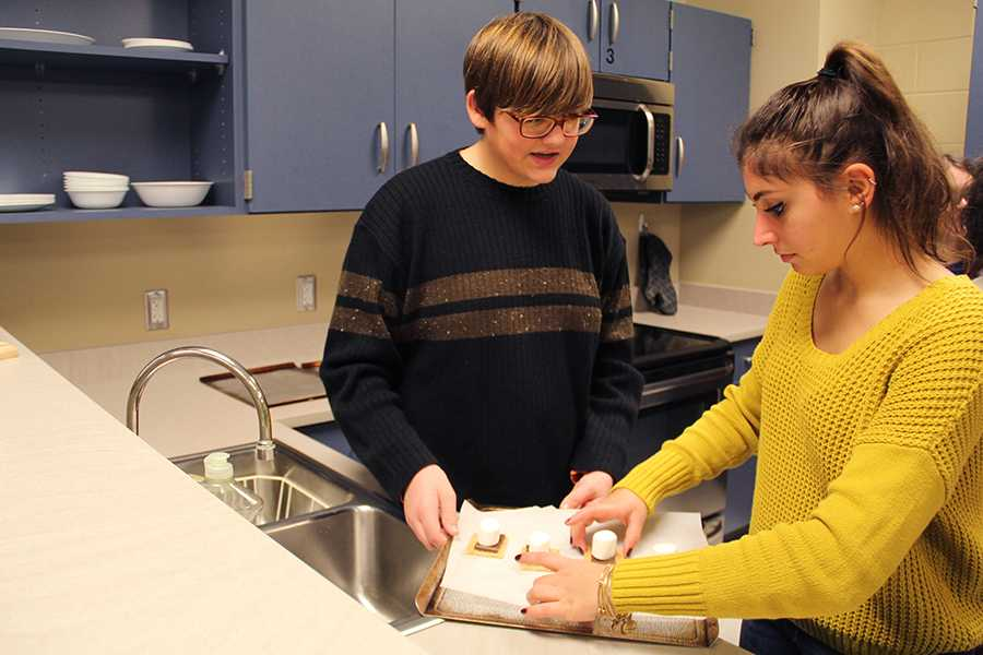 Alexa Adams (12) and Jacob Bailey (9) prepare s'mores at the Best Buddies meeting. The club meets every white day Monday and does various activities together.