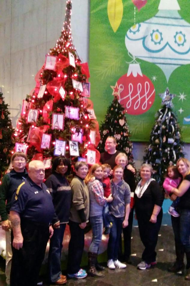 AATF members and friends take a picture by the French themed tree.  The tree will be on display until January 3, 2016.