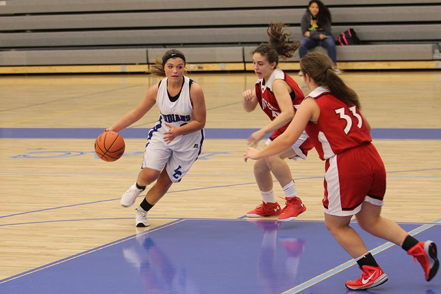 Alayna+Hand+%289%29+dribbles+the+ball+in+for+a+shot.+Munster+players+lunged+toward+her+on+defense.