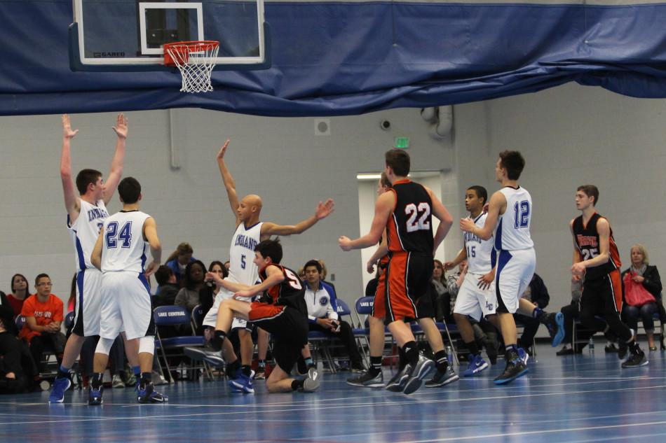 Freshman boys basketball players all stand under the opposing team's basket. LC boys were playing defense.
