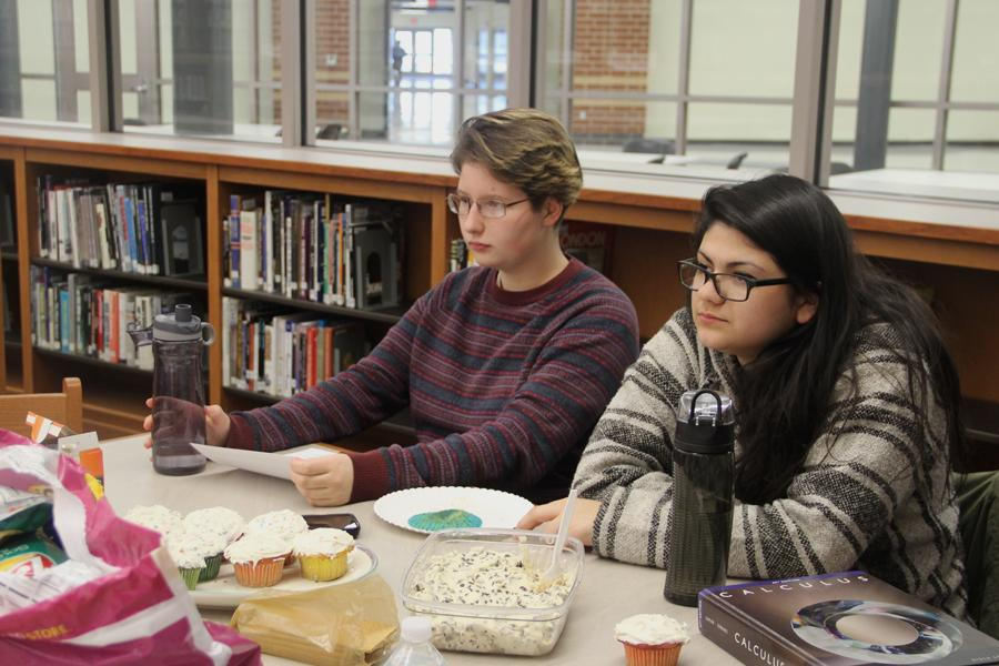 "Madelyn Nohos (11) and Leslie Lopez (12) listen to members of Book Club discuss the book ""Animal Farm."" Nohos and Lopez made cupcakes to bring to the meeting."