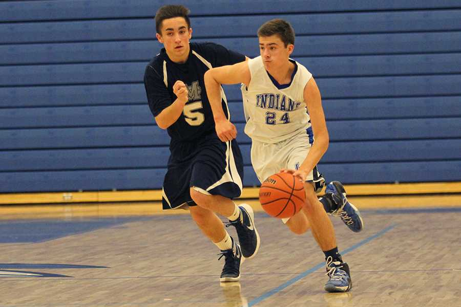 Zachary Dobos (9) dribbles the ball past an offender. The boys beat Michigan City with a final score of 62-31.