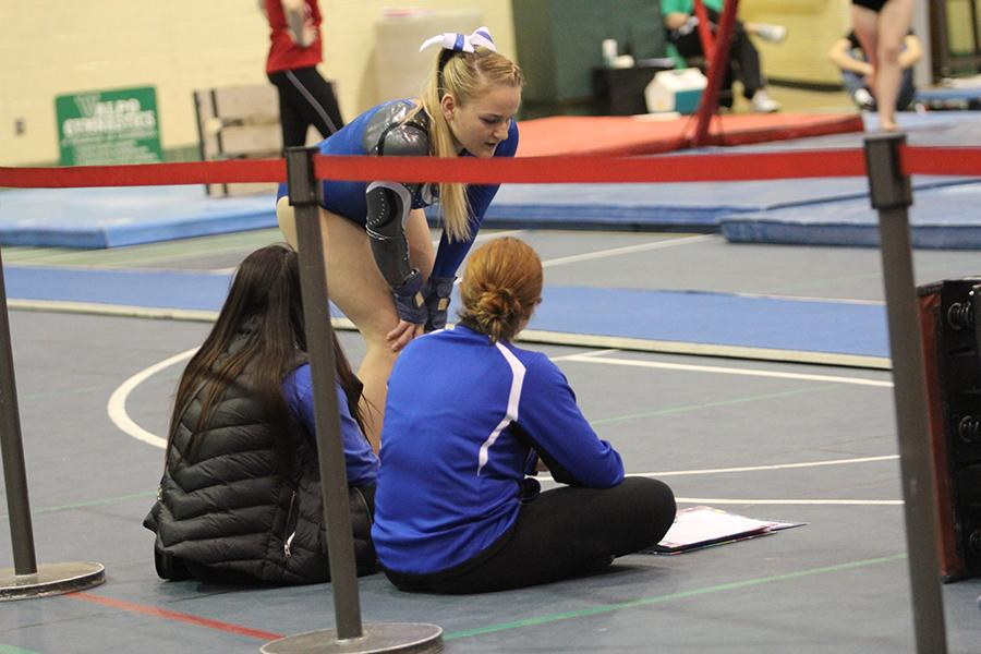 Megan+Gora+%2812%29+talks+to+her+coach+before+she+performs+on+the+vault.+Gora+landed+both+of+her+skills.