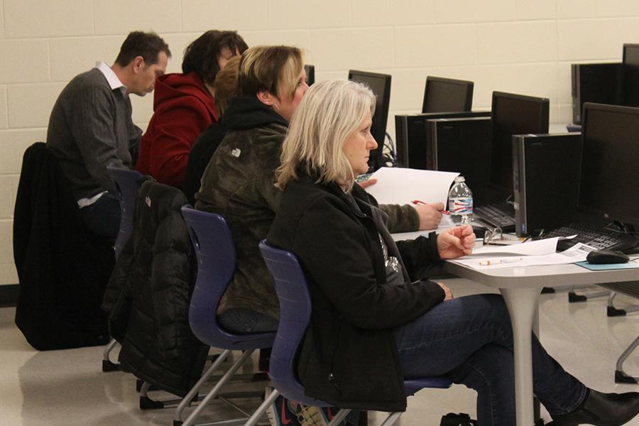 Parents take notes at the Dollars for Scholars parent meeting on Thursday, Feb. 18, in the library. At the meeting, DFS officers and school guidance counselors explained the new technological tools that the school has adopted for the upcoming school year.
