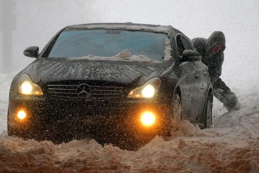 Two people work together trying to extract their a Mercedes Benz rear-wheel drive car that kept spinning wheels on U.S. Route 40 in Baltimore on Saturday, Jan. 23, 2016, during a powerful weekend storm blanketing the East Coast in snow. (Used with limited license: Karl Merton Ferron/Baltimore Sun/TNS)