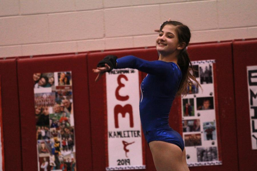Gabrielle DeVries (9) smiles after she completes her routine. DeVries made the varsity gymnastics team as a freshman.