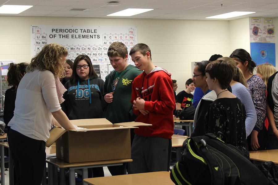 Mrs. Katelin Ellis, Science, begins to distribute T-shirts to Science Club members. The students planned on tie-dyeing the shirts in the future.