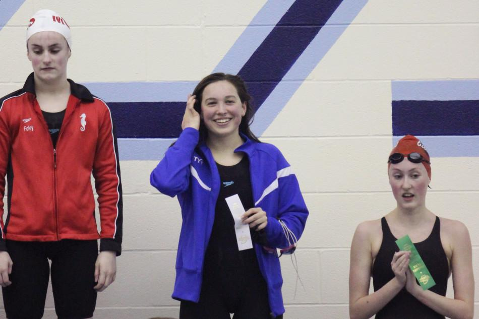 Julianna Massa (10) stands on the winners' podium after receiving a third place ribbon. The varsity girls swim team ended up placing third overall at Sectionals.