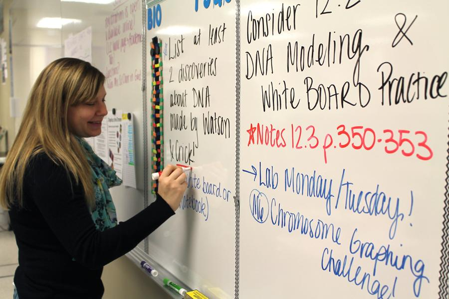 Ms. Gabby Rapin, Science, writes the agenda for the day on the whiteboard, although her Genetics classes often work at their own pace. She taught Genetics for the first time beginning last semester and had to organize the content without a useful textbook to reference.