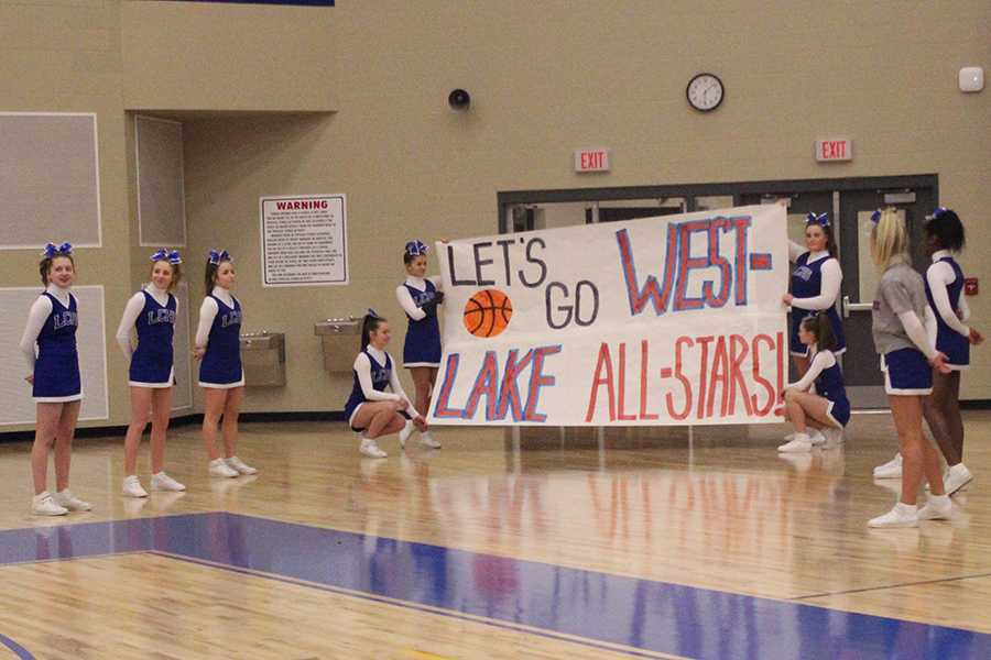 The+cheerleaders+hold+a+sign+for+the+West+Lake+basketball+team+to+run+through.+Posters+were+hung+all+around+the+gym+for+both+the+basketball+team+as+well+as+Best+Buddies.+