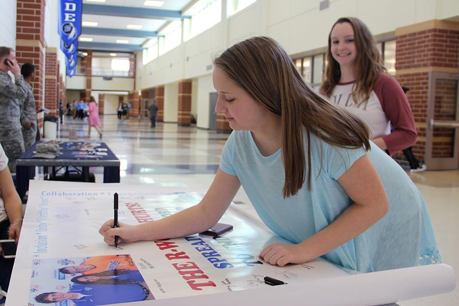 Kellie Repasi (11) signs the R-Word Banner. The banner was out at lunches on March 8 and 10.