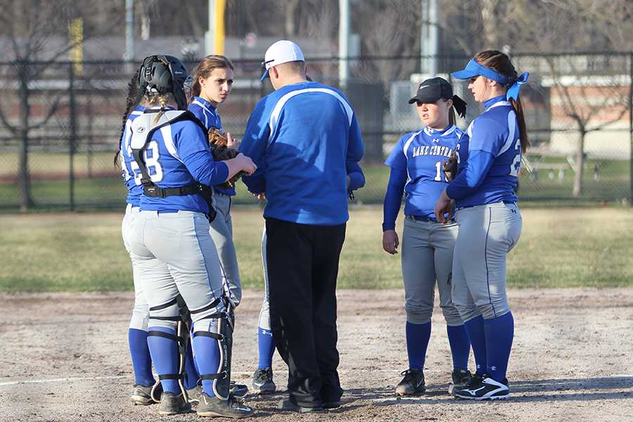 Varsity players strategize with Coach Jeff Sherman, Math. The team beat Munster 9-3.