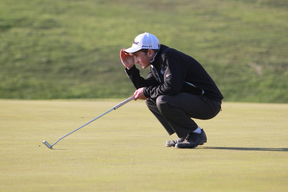 Nicholas Good (12) gets down to line up his shot. Good has been on the golf team since his freshman year.