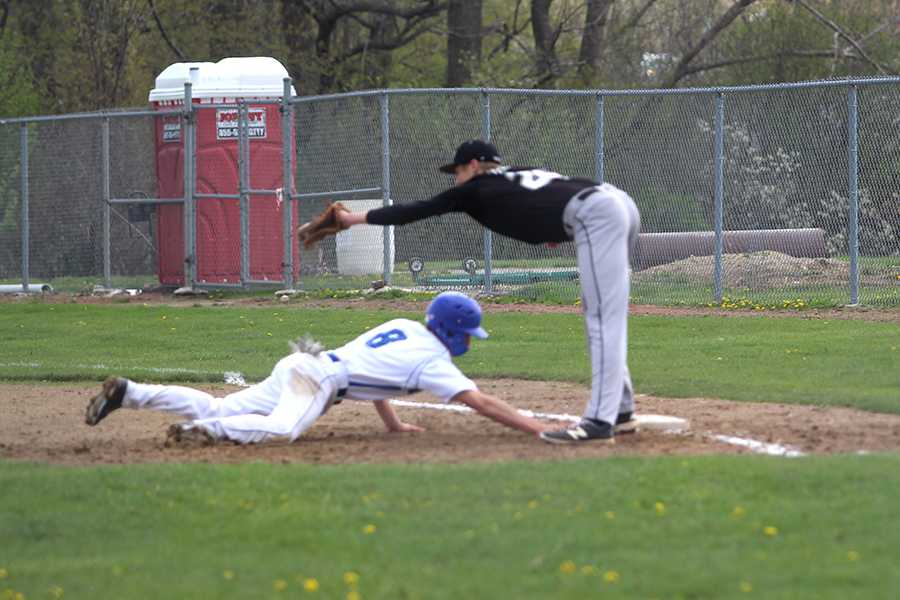 Raymond Hilbrich (10) dives back to first base.  Hilbrich dove back in time and was safe.